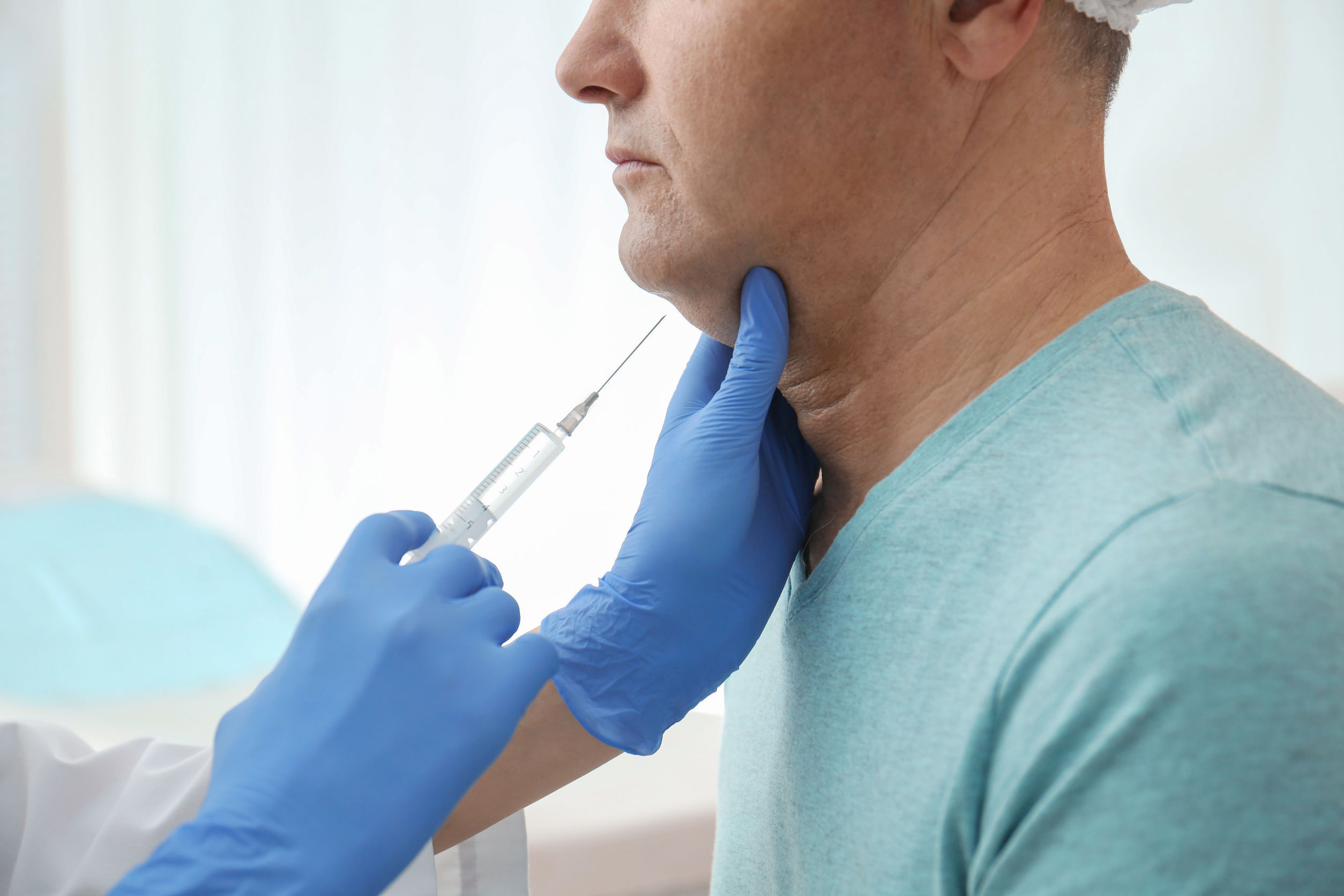 Mature man with double chin receiving injection in clinic, close