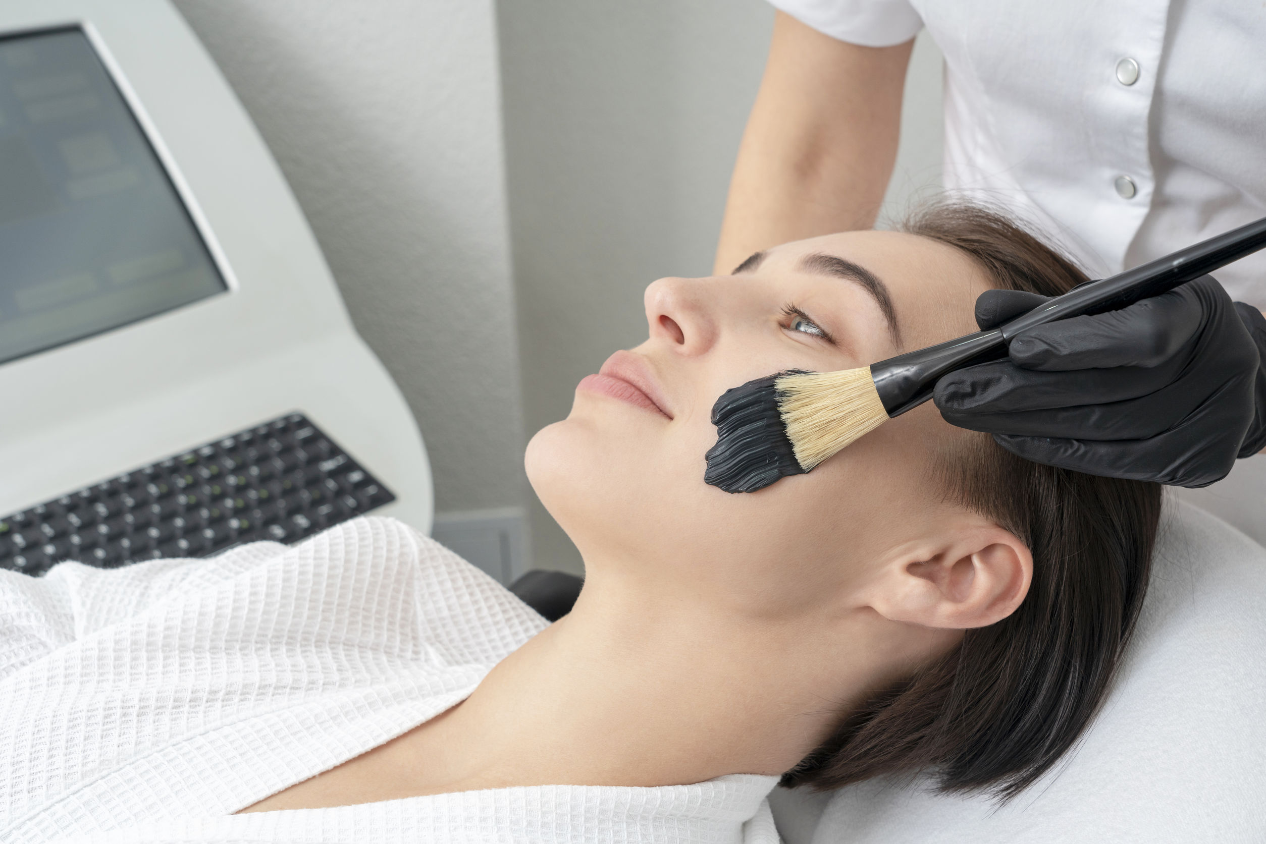 Cosmetologist applying black mask on the face of a beautiful mature woman for carbon peeling